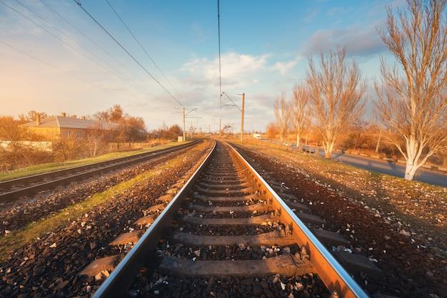 Paisaje industrial con estación de ferrocarril al atardecer