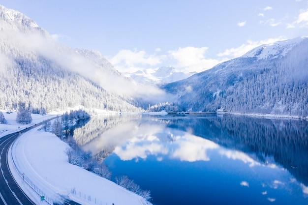 Paisaje invernal con brumosa montaña neblinosa y pintoresco lago de montaña de cristal