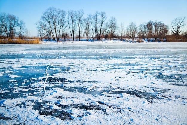 Paisaje invernal, lago congelado cubierto de hielo y nieve, árboles de fondo sin hojas y cielo azul claro