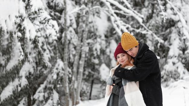 Paisaje invernal con pareja abrazándose