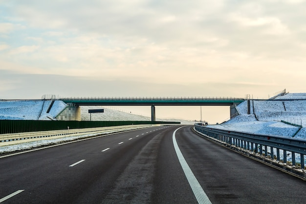 Paisaje de invierno con carretera asfaltada al horizonte.