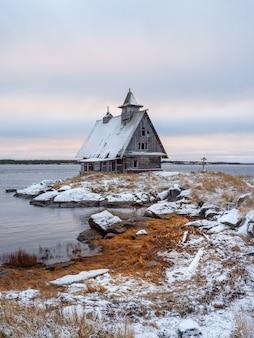 Paisaje de invierno nevado minimalista con auténtica casa en la orilla en el pueblo ruso rabocheostrovsk.