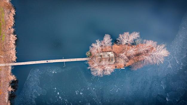 Paisaje de la mañana, pabellón de caza de madera, en una pequeña isla artificial. una plataforma de madera está llegando a la casa, abedules están creciendo a ambos lados