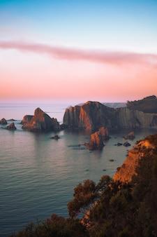 Paisaje marino con acantilados durante la puesta de sol, papel tapiz perfecto