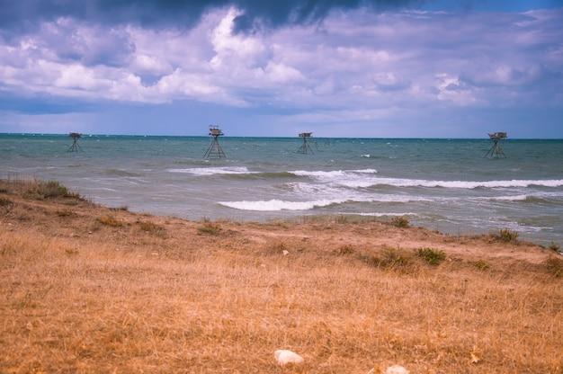 Paisaje marino con aparejos de pesca. cielo tormentoso. costa oeste de crimea.