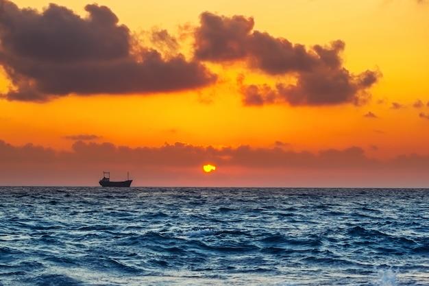 Paisaje marino con buque de carga en la hora del atardecer