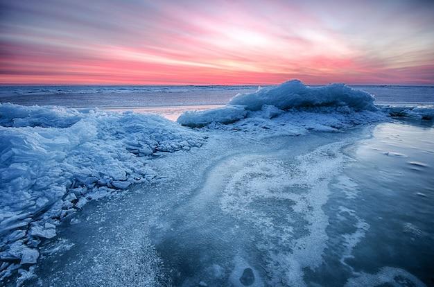 El paisaje marino congelado abstracto de la salida del sol del invierno con hielo y coloreó el cielo.
