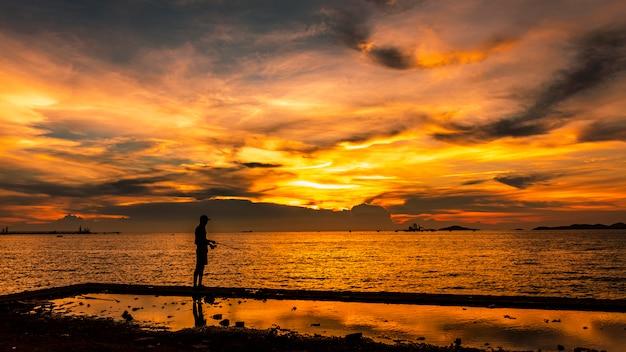 Paisaje marino crepuscular el atardecer y la luz dorada con silueta de pescador en primer plano