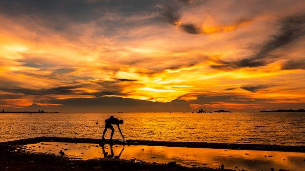 Paisaje marino crepuscular la puesta del sol y la luz dorada con silueta de pescador en primer plano en la isla en tailandia