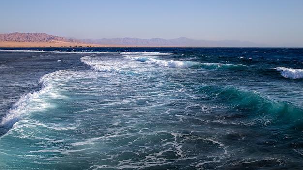 Paisaje marino con olas con textura y siluetas de montaña en el horizonte.