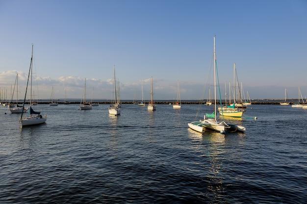 Paisaje minimalista con barcos en el hermoso puerto de marina bay en el océano