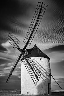 Paisaje de molinos de viento en un día nublado en un campo árido en blanco y negro