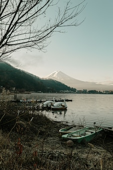 Paisaje de la montaña de fuji y del lago kawaguchiko con los barcos en la salida del sol de la mañana, estaciones del invierno en yamanachi, japón.