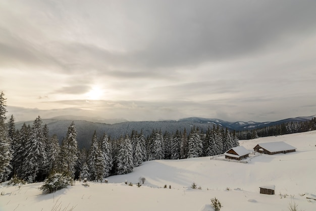 Paisaje de montaña de invierno. casas de madera viejas en el claro nevoso en el fondo del canto de la montaña, el bosque spruce y el cielo nublado. feliz año nuevo y feliz navidad tarjeta.