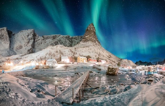 Paisaje de montaña nevada con aurora boreal en pueblo escandinavo