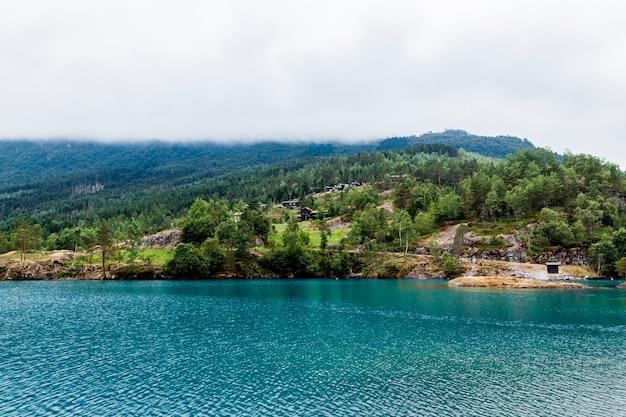 Paisaje de montaña verde con lago idílico azul