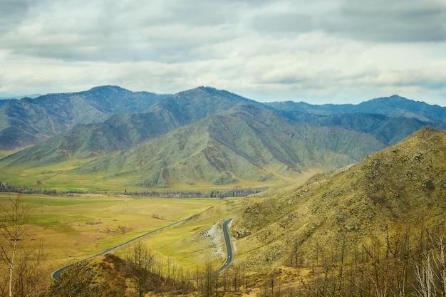 Paisaje con montañas, bosque, pradera en frente. hermoso paisaje