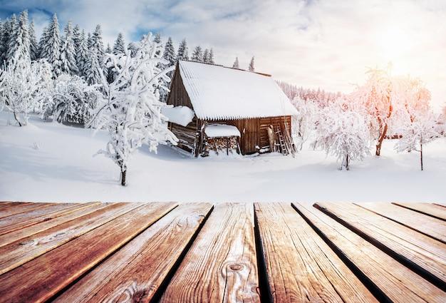 Paisaje de montañas de invierno con un bosque nevado y una cabaña de madera y mesa en mal estado.