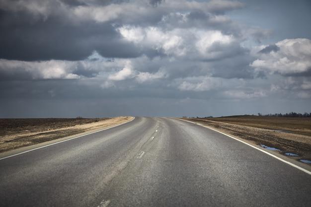 Paisaje natural con una carretera de asfalto que conduce hacia las nubes de tormenta