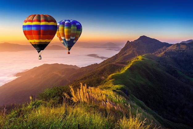 Paisaje de niebla matutina y montañas con globos aerostáticos al amanecer.