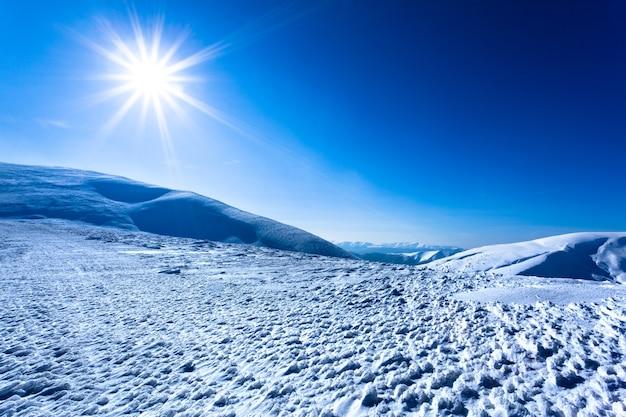Paisaje de nieve invierno valle y montañas y sol arriba en claro día helado de invierno