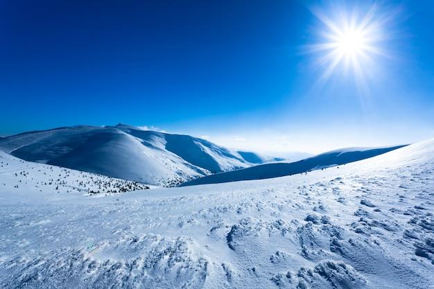 Paisaje de nieve invierno valle y montañas y sol arriba