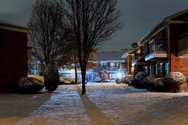 Paisaje nocturno de invierno: banco bajo árboles de invierno y brillantes luces de la calle con copos de nieve cayendo