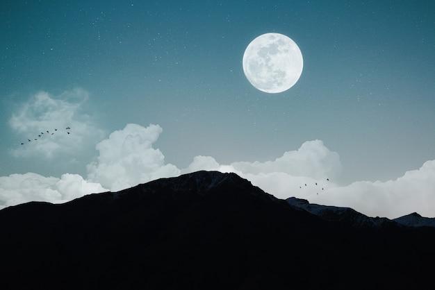 Paisaje nocturno con luna llena y cielo nublado.