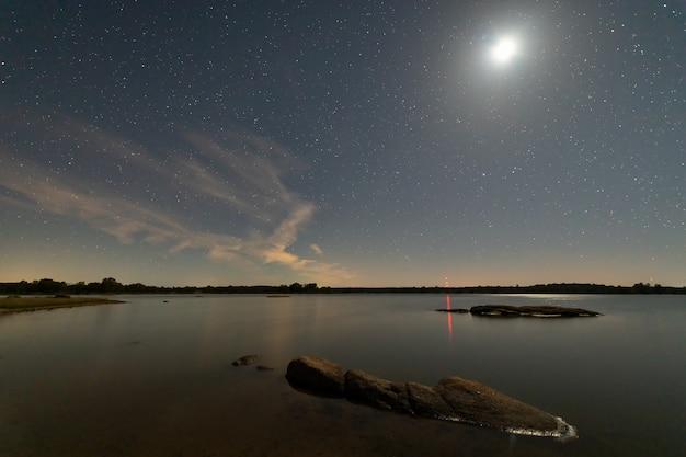 Paisaje nocturno con luna en el pantano de valdesalor. extremadura españa.