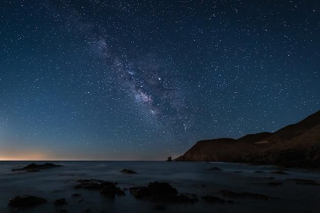 Paisaje nocturno con vía láctea en la costa de los escullos. parque natural de cabo de gata. españa.