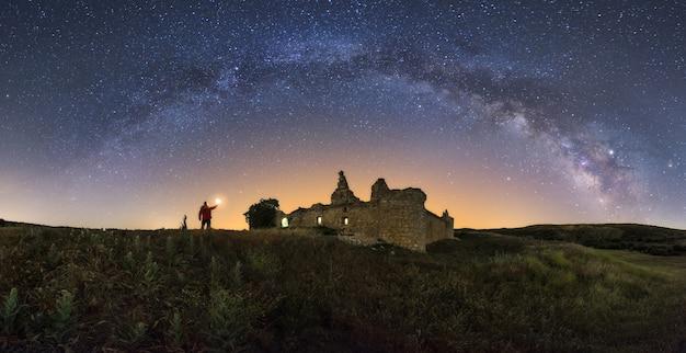 Paisaje nocturno con la vía láctea sobre un antiguo castillo.