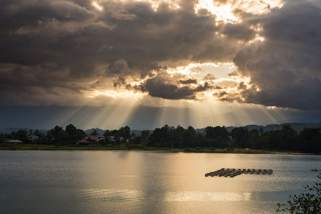 Paisaje con nubes y rayos de sol en el lago