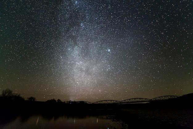 Paisaje de la orilla del río de guijarros, árboles en el horizonte, estrellas brillantes y galaxia de la vía láctea en el cielo oscuro reflejado en aguas tranquilas. belleza del concepto de naturaleza.