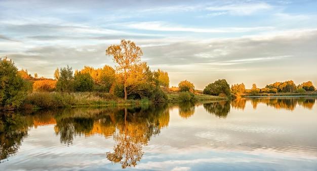 Paisaje otoñal con agua, árboles coloridos.