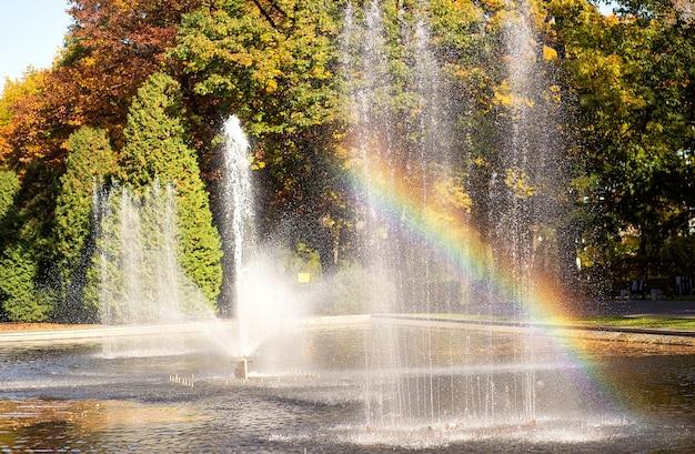 Paisaje otoñal con un hermoso arco iris en una fuente