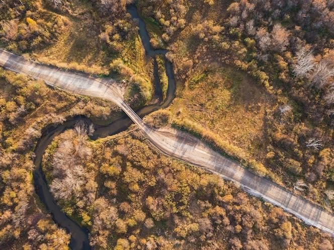 Paisaje otoñal con río y puente.