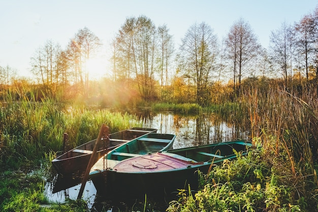 Paisaje de otoño en el río al atardecer con barcos