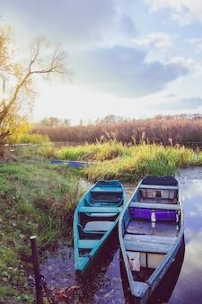 Paisaje en otoño en un río con barcos