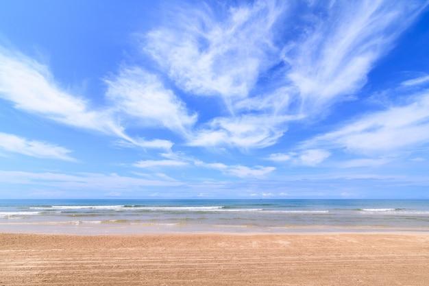 Paisaje de la playa de arena con cielo nuboso.