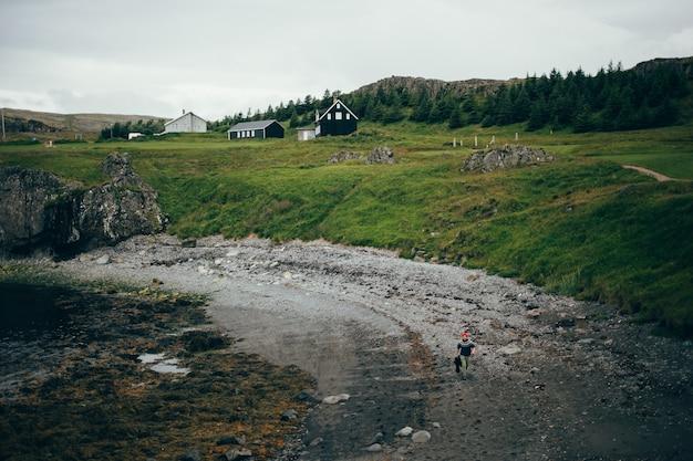Paisaje de playa islandesa, el hombre camina en suéter