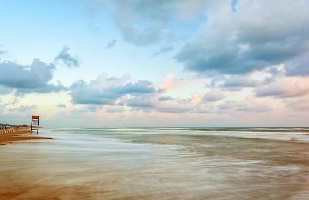 Paisaje de playa con mirador de madera.