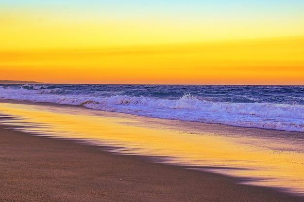 Paisaje de una playa rodeada de olas del mar durante una puesta de sol naranja en la noche
