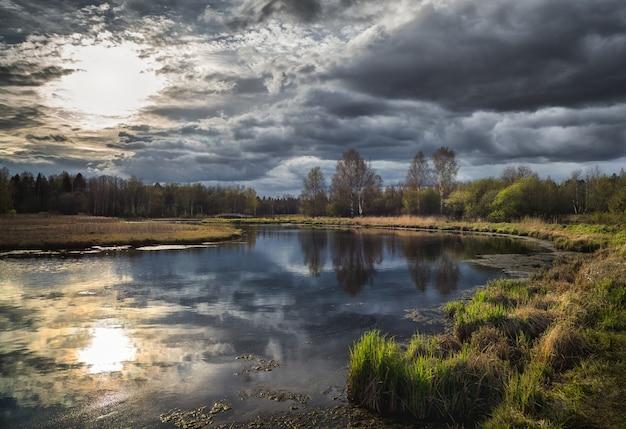 Paisaje de primavera rusa con sol y reflejos de árboles en el lago