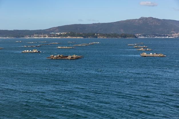 Paisaje de la ría de arousa con numerosas plataformas para el cultivo de mejillones flotando en el mar. illa de arousa, galicia, españa
