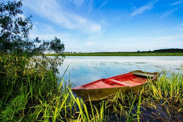 Paisaje del río con un bote rojo en el río