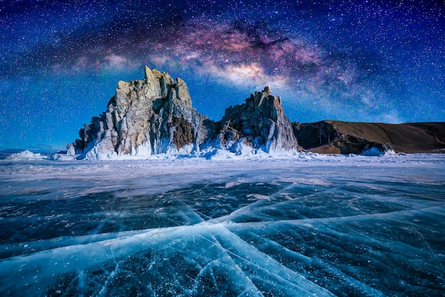 Paisaje de la roca y de la vía láctea de shamanka en el cielo con hielo de fractura natural en agua congelada en el lago baikal, siberia, rusia.