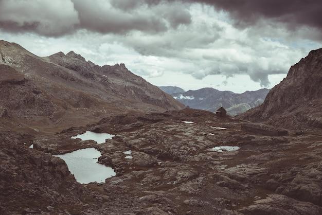 Paisaje rocoso de gran altitud y pequeño lago. majestuoso paisaje alpino con espectacular cielo tormentoso. visión gran angular desde arriba, imagen en tonos, filtro vintage, tonos divididos.