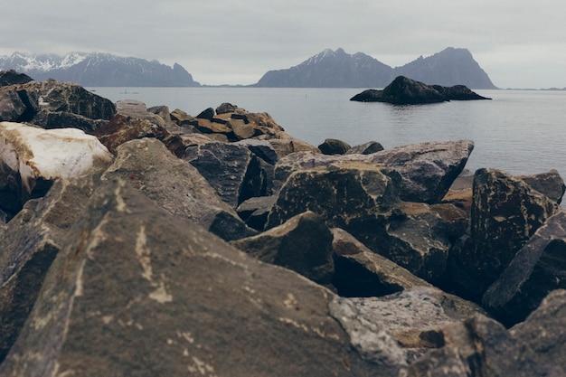 Paisaje salvaje de la costa rocosa con isla solitaria un día de niebla y frío nublado.