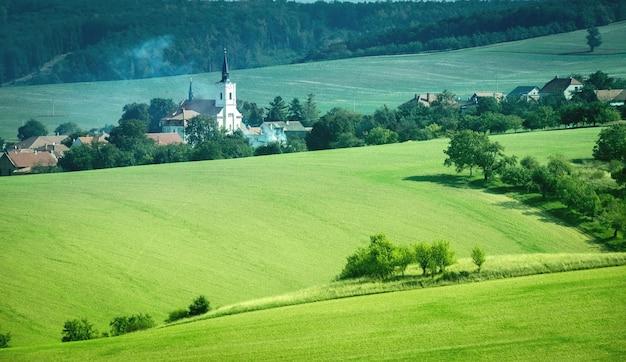 Paisaje de sol de laderas verdes y castillo blanco