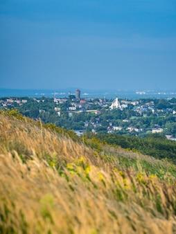 Paisaje soleado de una ladera de hierba en el fondo del paisaje urbano de laziska gorne en polonia